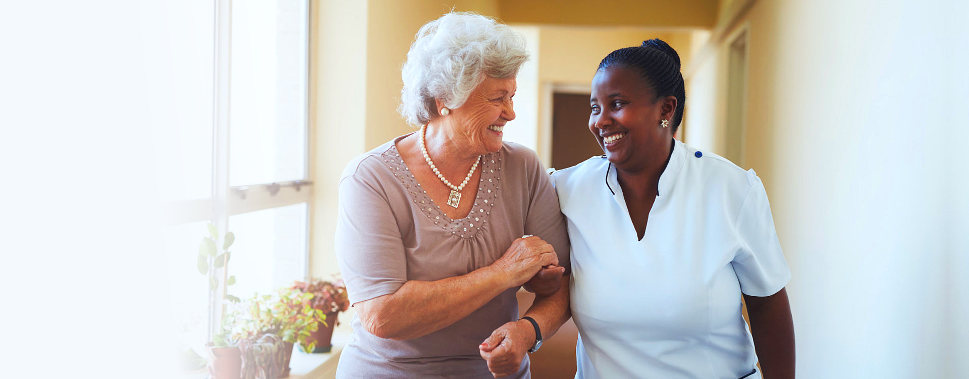 caretaker and patient looking at each other and smiling