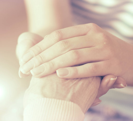 caregiver holding her patient hand
